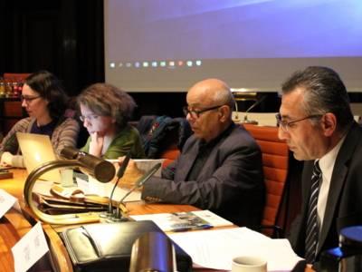 Zwei Frauen und zwei Männer sitzen in einer Reihe hinter Pulten im Hodlersaal nebeneinander und blicken auf Unterlagen, die vor ihnen liegen.