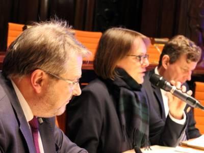 Drei Personen - zwei Männer und eine Frau - sitzen im Hodlersaal hinter Pulten. Die Frau in der Mitte spricht in ein Mikrofon, das sie in der Hand hält.