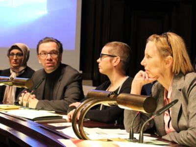 Vier Personen - drei Frauen und ein Mann - sitzen nebeneinander