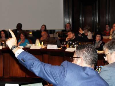 Zwei von etwa 15 Personen, die auf gegenüberliegenden Seiten der kreisförmig aufgestellten Pulte im Hodlersaal des Neuen Rathauses sitzen, signalisieren mit erhobenem Arm, dass sie auf die Redeliste gesetzt werden möchten.
