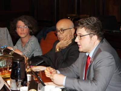 Drei Personen - zwei Männer und eine Frau - sitzen im Hodlersaal des Neuen Rathauses nebeneinander hinter Pulten. Der Mann rechts spricht.