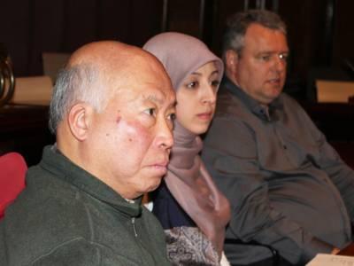 Drei Personen - zwei Männer und eine Frau - sitzen im Hodlersaal hinter Pulten und blicken nach vorn.