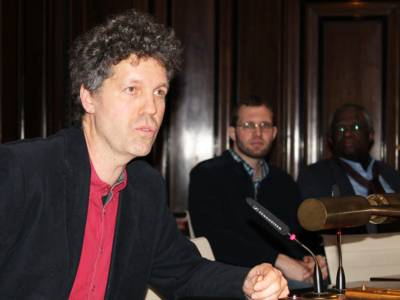 Ein Mann sitzt im Holdlersaal hinter einem Pult und spricht.