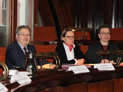Drei Personen - zwei Männer und eine Frau - sitzen Im Hodlersaal im Neuen Rathaus hinter Pulten und blicken nach vorne.