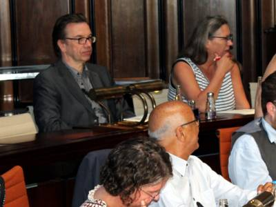 Vier Personen sitzen in zwei Reihen im Hodlersaal des Neuen Rathauses hinter Pulten.