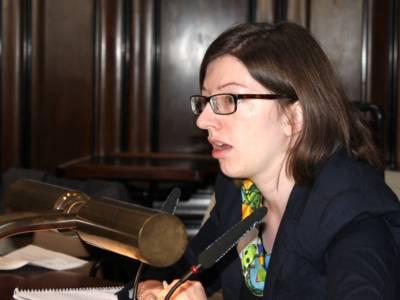 Eine Frau sitzt im Hodlersaal des Neuen Rathauses hinter einem Pult und spricht.