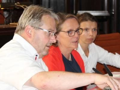 Drei Personen - zwei Frauen und ein Mann - sitzen im Hodlersaal hinter Pulten. Die Frau in der Mitte spricht.