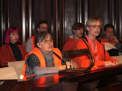 Sechs mit Schwimm- und Warnwesten bekleidete Personen sitzen im Hodlersaal neben- und hintereinander. Eine Frau in der vorderen Reihe spricht in ein Mikrofon.