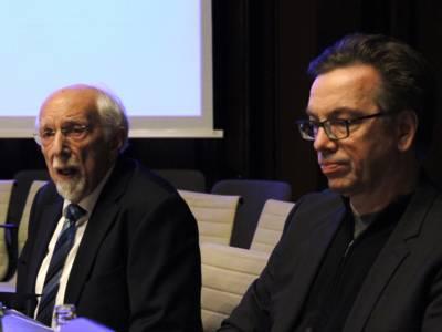 Zwei Männer sitzen im Hodlersaal des Neuen Rathauses hinter Pulten. Der Linke spricht.