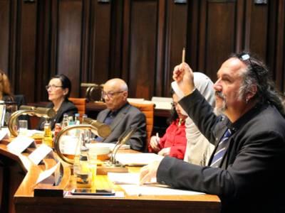 Sechs Personen, davon 4 Frauen und zwei Männer sitzen im Hodlersaal hinter Pulten. Ein Mann rechts im Bild hebt die Hand hoch, um einen Redebeitrag zu signalisieren. In der Hand hält er einen Stift.