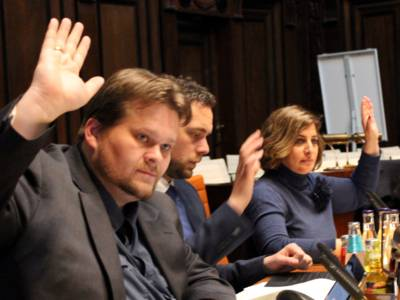 Drei Personen - eine Frau und zwei Männer - sitzen im Hodlersaal nebeneinander hinter Pulten und heben die Hand zur Abstimmung hoch.