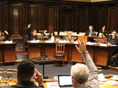 Etwa 20 Personen sitzen im Hodlersaal des neuen Rathauses. Die meisten davon heben ihre Hand, um ihre Zustimmung zu signalisieren.