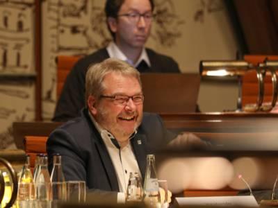 Ein Mann sitzt im Hodlersaal hinter einem Pult und lacht.