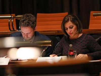 Ein Mann und eine Frau sitzen im Hodlersaal hinter Pulten und blicken auf Papiere, die vor ihnen liegen.