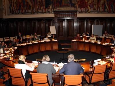 Etwa 20 Personen sitzen an kreisförmig aufgestellen Pulten im Hodlersaal des Neuen Rathauses.