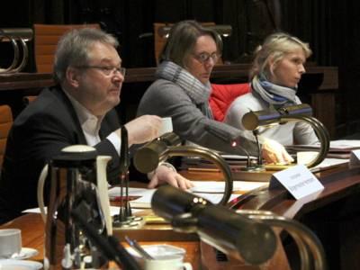 Zwei Frauen und ein Mann sitzen im Hodlersaal des Neuen Rathauses hinter Pulten. Der mann hält eine Kaffeetasse in der Hand. Alle drei blicken nach vorn.