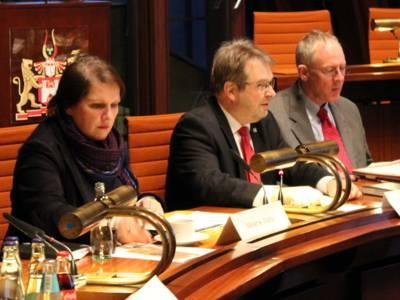 Drei Personen - eine Frau und zwei Männer - sitzen nebeneinander hinter Pulten im Hodlersaal. Die Frau schaut nach unten rechts, die Männer schauen nach vorne.