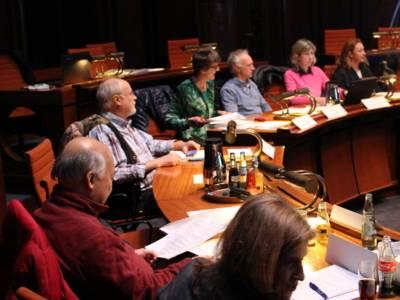 Sieben Personen sitzen im Viertelkreis hinter Pulten im Hodlersaal
