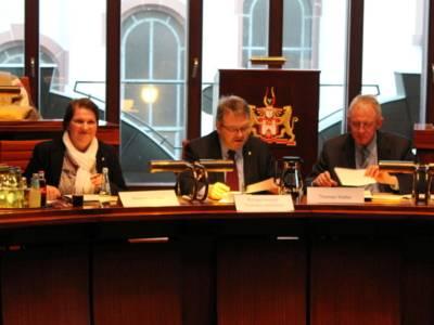 Drei Personen - eine Frau und zwei Männer - sitzen hinter Pulten. Die Frau links schaut zur Seite, die beiden Männer schauen auf Papiere, die vor ihnen auf dem Tisch liegen.