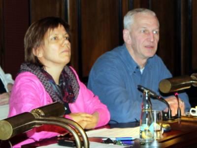 Zwei Personen - eine Frau und ein Mann - sitzen hinter Pulten. Der Mann spricht und blickt nach vorne.
