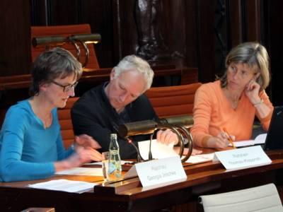 Drei Personen sitzen nebeneinander hinter Pulten. Die linke und die mittlere Personen schauen auf ein Papier, das vor der linken liegt. Die rechte schaut zur mittleren Person.
