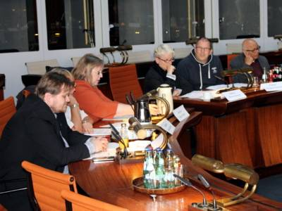 Sechs Personen sitzen im Drittelkreis hinter Pulten im Hodlersaal.