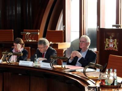 Drei Personen sitzen im Hodlersaal hinter Pulten. Die linke und die mittlere schauen auf Papiere, die vor ihnen liegen, die rechte Person schaut nach vorne.