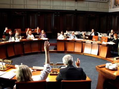 Etwa 15 Personen sitzen im Hodlersaal hinter kreisförmig aufgestellten Pulten. Die Personen im inneren Kreis heben die Hände zur Abstimmung.