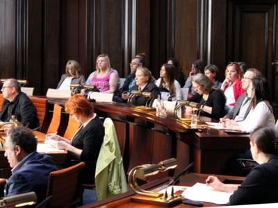 Etwa 20 Personen sitzen teilweise hinter Pulten, teilweise in Stuhlreihen dahinter und blicken nach vorne. Einige davon schauen in Unterlagen, die vor ihnen liegen.
