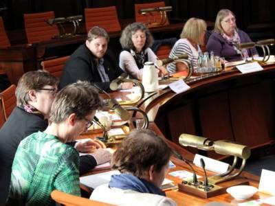 SIeben Personen sitzen im Hodlersaal des Neuen Rathauses hinter Pulten. Einige davon schauen auf Unterlagen, die vor ihnen liegen.