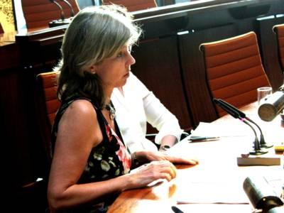 Eine Frau sitzt im Hodlersaal hinter einem Pult und spricht in ein Tischmikrofon. Dahinter sitzt eine weitere Person, die durch die Erste im Bild verdeckt ist.