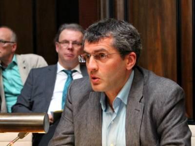 Ein Mann mit Brille sitzt im Hodlersaal und blickt nach vorne, während er spricht.. Hinter ihm sind zwei weitere sitzende Männer erkennbar.