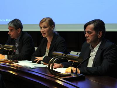 Drei Personen - zwei Männer und eine Frau sitzen im Hodlersaal hinter Pulten. Die Frau in der Mitte spricht.
