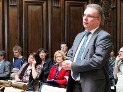 Eine Mann mit Brille steht im Hodlersaal vor einem Pult und spricht.
