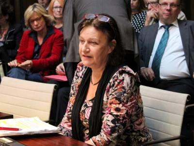 Eine Frau sitzt im Hodlersaal und spricht. Dabei trägt sie ihre Brille über der Stirn. Hinter ihr sind ca. acht weitere Personen erkennbar.