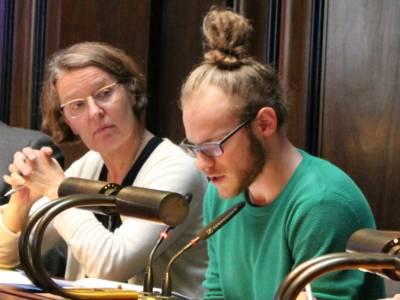 Zwei Personen sitzen im Hodlersaal hinter Pulten. Die Rechte - ein Mann - schaut auf ein Papier vor sich und spricht. Die Frau links daneben blickt zu ihm.