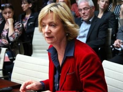 Eine Frau sitzt im Holdersaal hinter einem Pult und spricht. Hinter ihr sind etwa acht weitere Personen erkennbar.