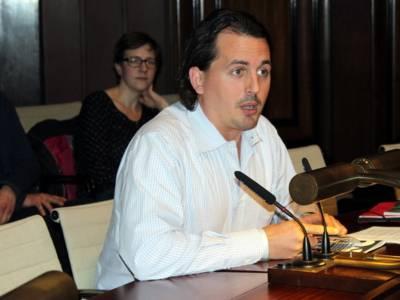 Ein Mann sitzt im Hodlersaal hinter einem Pult und spricht.