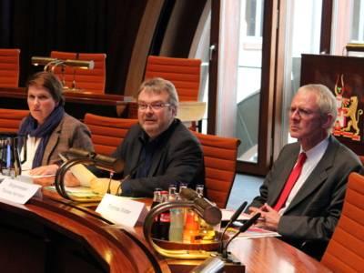 Drei Personen sitzen in Hodlersaal hinter Pulten. EIn Mann in der Mitte spricht und blickt dabei nach links.