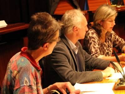 Drei Personen - zwei Frauen und ein Mann - sitzen nebeneinander hinter Pulten. Die rechte Frau spricht.