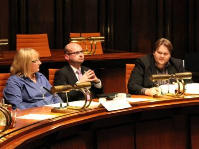 Drei Personen - eine Frau und zwei Männer - sitzen nebeneinander hinter Pulten. Der rechte Mann spricht, der Mittlere hält die Fingerspitzen beider Hände aufeinander auf Brusthöhe und blickt schräg nach oben. Die Frau links blickt zu dem sprechenden Mann.