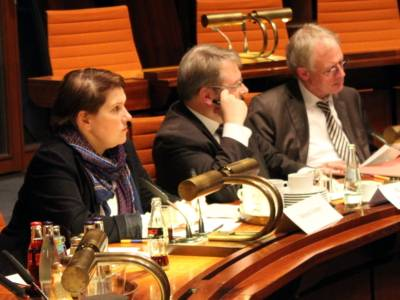 Drei Personen sitzen nebeneinander hinter Pulten. Die Frau und ein Mann blicken nach vorne, der Mann rechts blickt auf Papiere, die vor ihm auf dem Pult liegen.