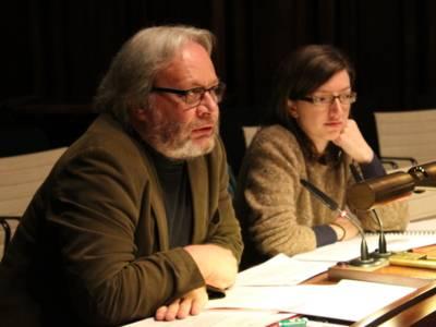 Ein Mann und eine Frau sitzen nebeneinander hinter Pulten. Der Mann links spricht.