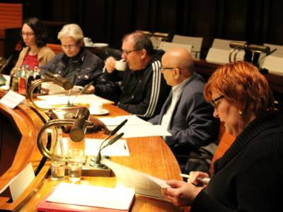 Fünf Personen - drei Frauen und zwei Männer - sitzen nebeneinander hinter Pulten. Die Frau rechts im Bild blickt auf Papiere, die vor ihr auf dem Pult liegen und spricht.
