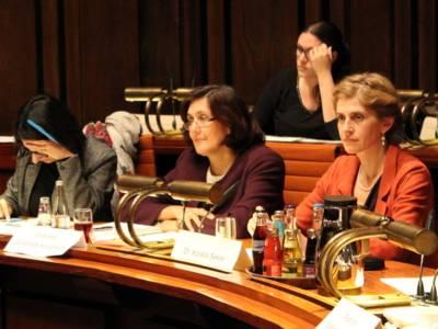 Zwei Frauen und ein Mann sitzen nebeneinander hinter Pulten. In der Reihe dahinter sitzt eine weitere Frau.