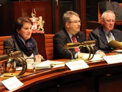 Drei Personen - eine Frau und zwei Männer - sitzen nebeneinander hinter Pulten im Hodlersaal