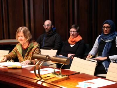 Eine Frau sitzt im Hodlersaal hinter einem Pult und spricht in ein Mikrofon. Hinter ihr sind drei weitere Personen erkennbar.