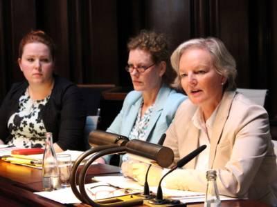 Drei Frauen sitzen im Hodlersaal hinter Pulten. Die rechte Frau spricht.