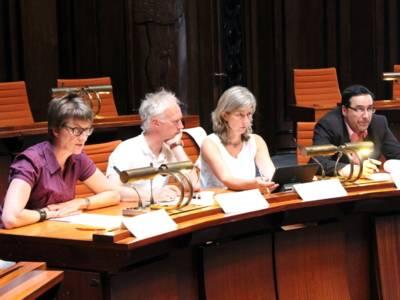 Vier Personen - zwei Frauen und zwei Männer - sitzen im Hodlersaal hinter Pulten. Die Frau links spricht in ein am Tisch befestigtes Mikrofon.