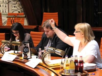 Drei Personen - zwei Frauen und ein Mann - sitzen im Hodlersaal hinter Pulten. Die Frau links und der mann in der Mitte blicken auf Papiere, die vor ihnen auf dem Tisch liegen und die Frau rechts hebt den Arm, um einen Redebeitrag zu signalisieren.